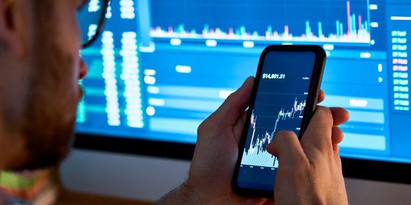 Trader analizuje wykresy na telefonie i komputerze, aby wykorzystać Pivoi Points